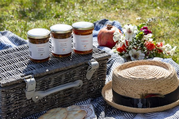 Hamper of authentic Italian produce, three jars sitting on a picnic hamper outside on a picnic blanket.